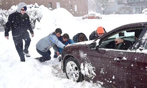 Wilkes Students Cody Morcom, Dylan Fox, Teddy Marines and Corey Cowitch assist a Wilkes-Barre resident whose car is stuck on S. Main St. The group spent their snow day driving around and helping perilled residents after their original plans to go sledding were cancelled.
