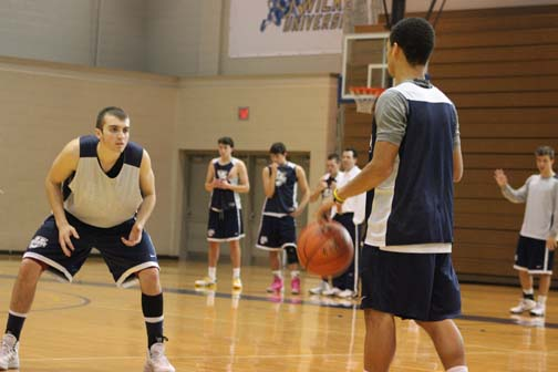 Guard Devin Dunn, at left, gets set on defense during a recent practice session for the Colonels at the Marts Center.  The 6-2 guard from Staten Island will be one of the team captains for the 2013-14 season.