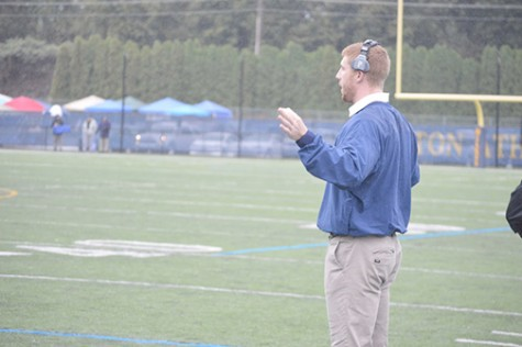 Hartman signaling the plays to his team members on the field from the sidelines.