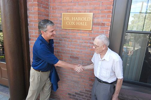 Dr. Cox and President Leahy shake hands at the dedication of Cox Hall.