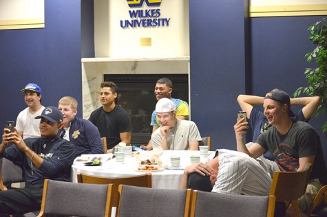 The baseball team reacts with laughter to Kramer's roast.