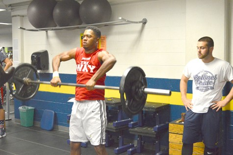Men's basketball freshman Marcus Robinson performs a hang clean as a part of his offseason workout at Martz.