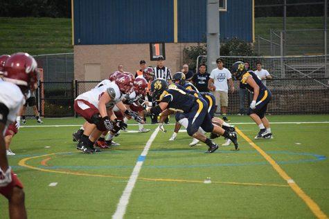 Members of Wilkes' offensive line look to gain ground against the Muhlenberg defenders.