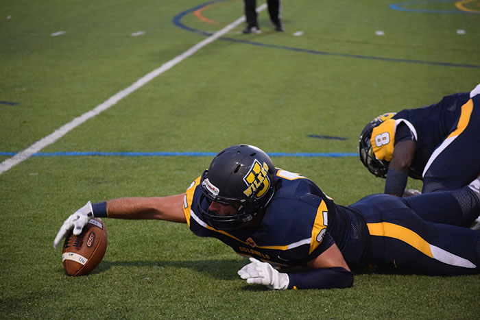 Sophomore Michael Murphy #25 dives for a loose ball in the home opener at Schmidt Stadium.