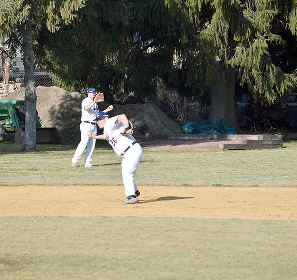#26 Joe Champi throws to first base.