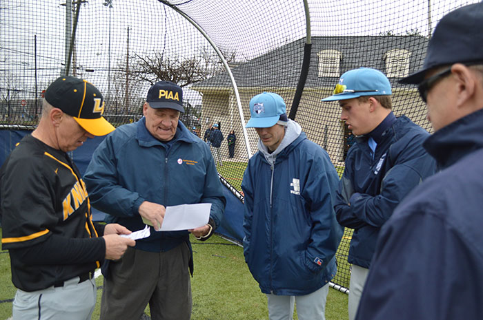 Home plate umpire Harry Kaskey, center-left, reviews line up cards at a plate conference with coaches.