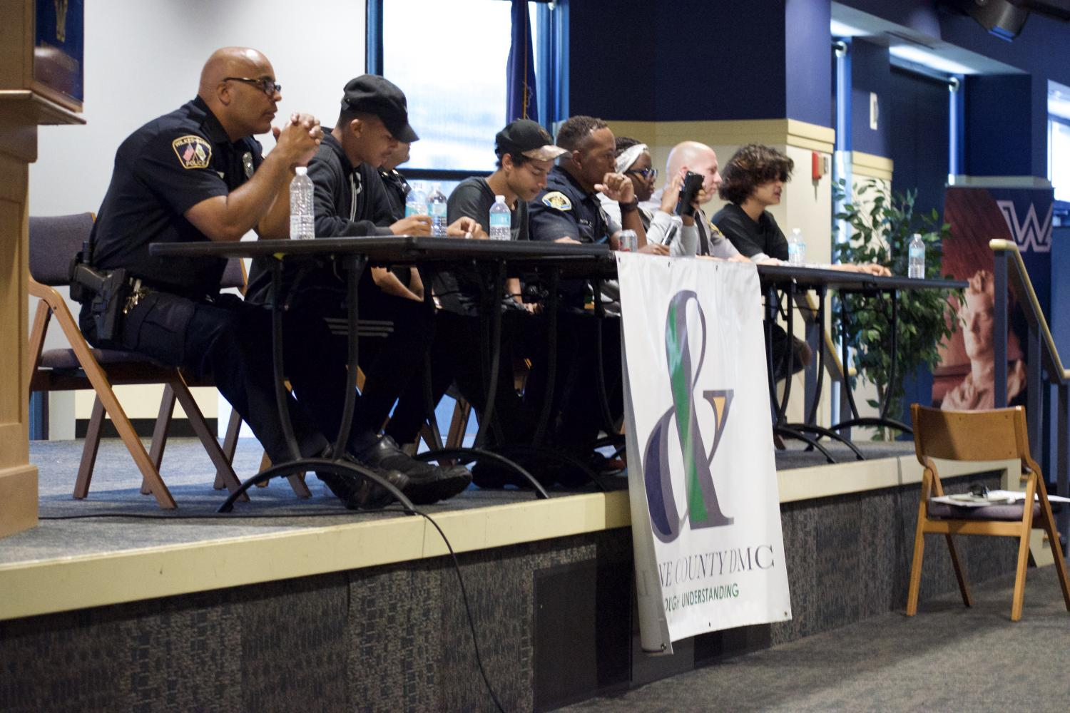 The panel of local police officers and youth working to reach an understanding through discussion of common misunderstandings in city crime.
