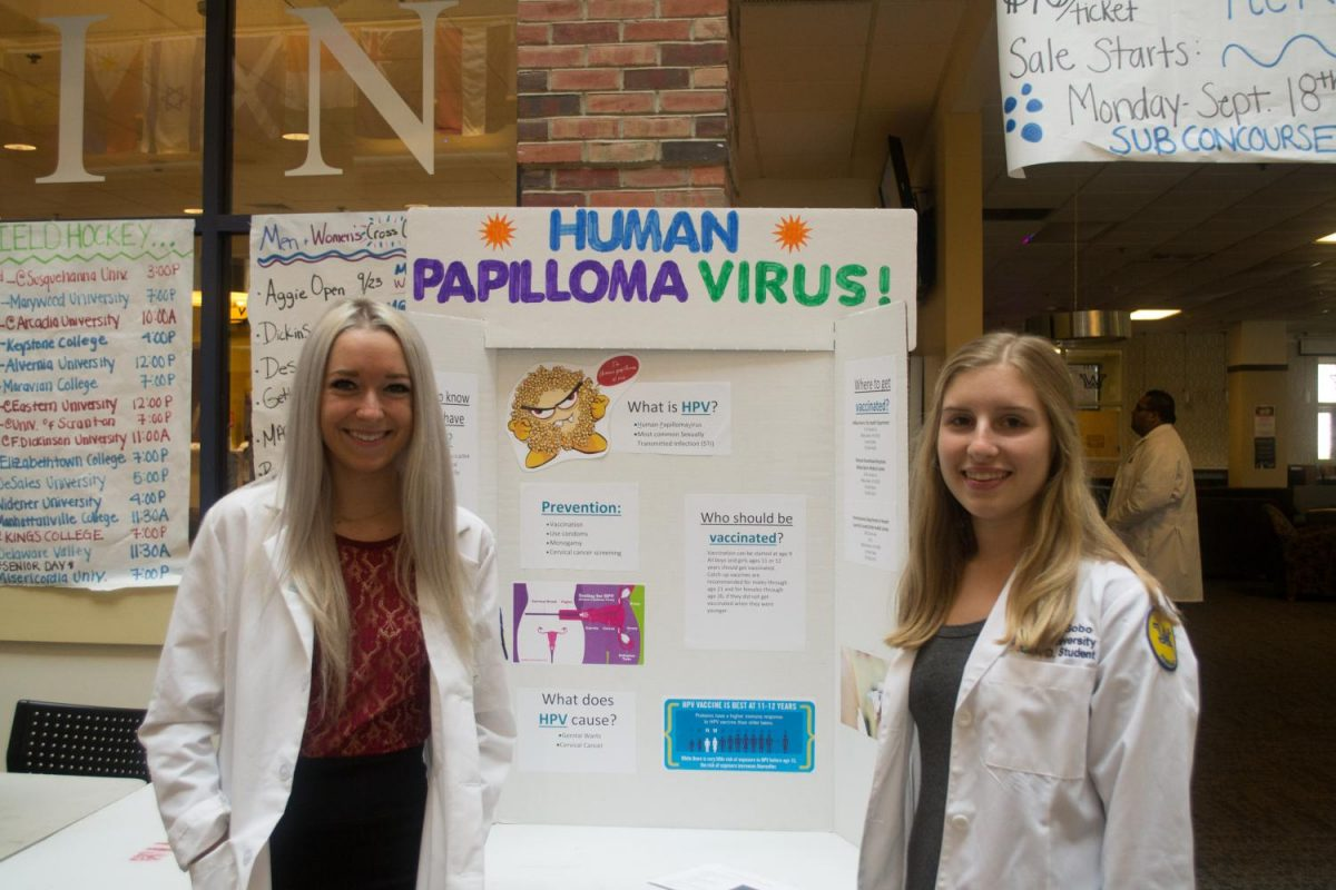 Pharmacy+students+Katie+Miller%2C+left%2C+and+Antonia+Gobo%2C+right%2C+stand+in+front+of+their+display+on+the+human+papilloma+virus%2C+a+sexually+transmitted+disease.+