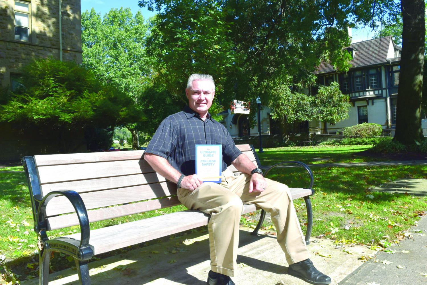 Public safety officer Peter J. Canavan stands with his newly published book on college campus safety.