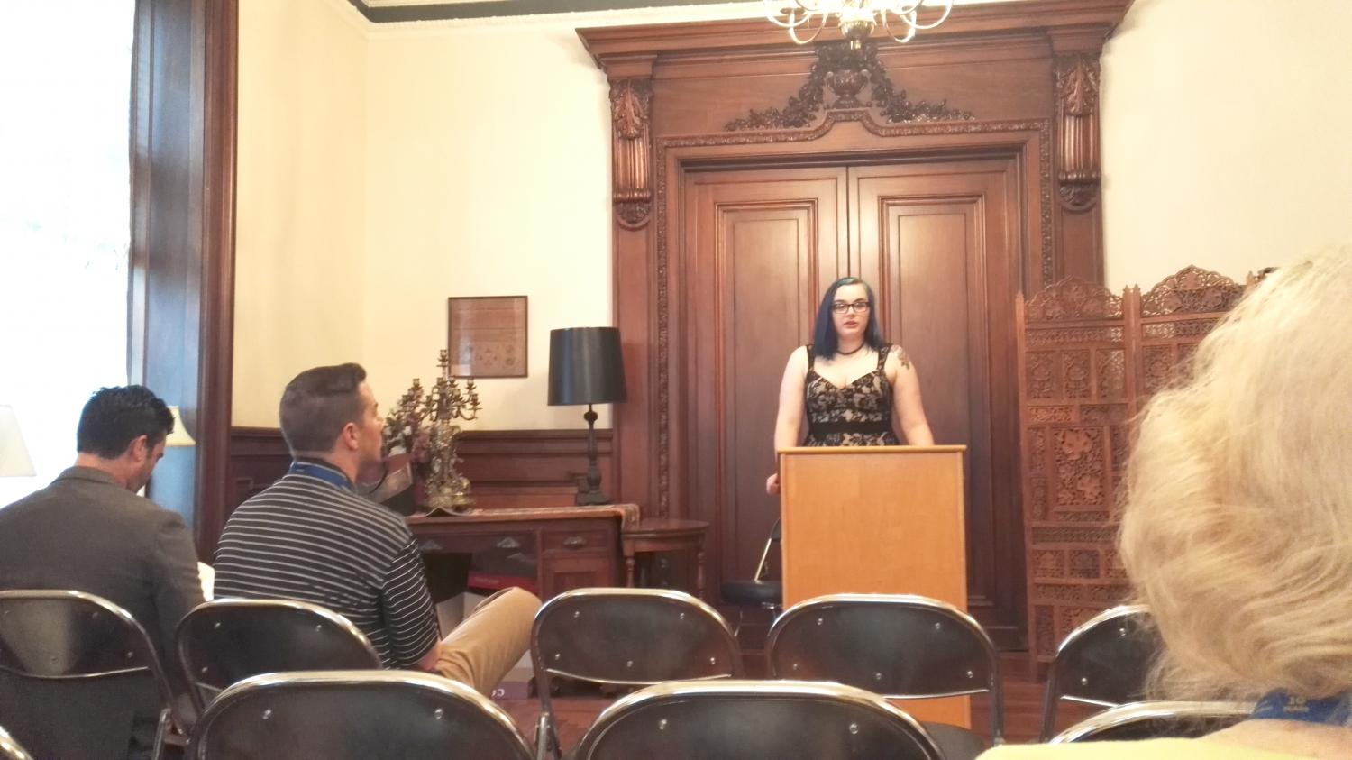 Elyse Guziewicz, the executive editor of the magazine, stands at the podium to introduce each speaker at the gathering.