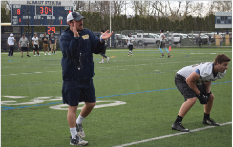 Coach Tom Elder giving instruction during a rainy spring practice.