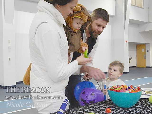 Wilkes+footballs+head+coach+Jonathan+Drach+and+his+family+pick+out+candy+from+one+of+the+tables.