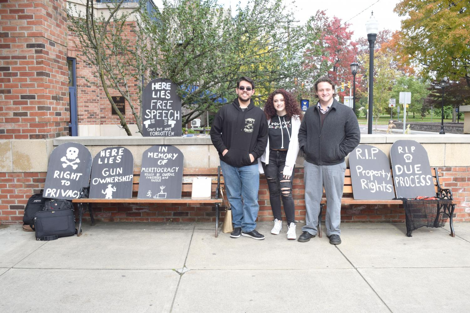Three Young Liberitarians pose in front of their constitutional rights posters.