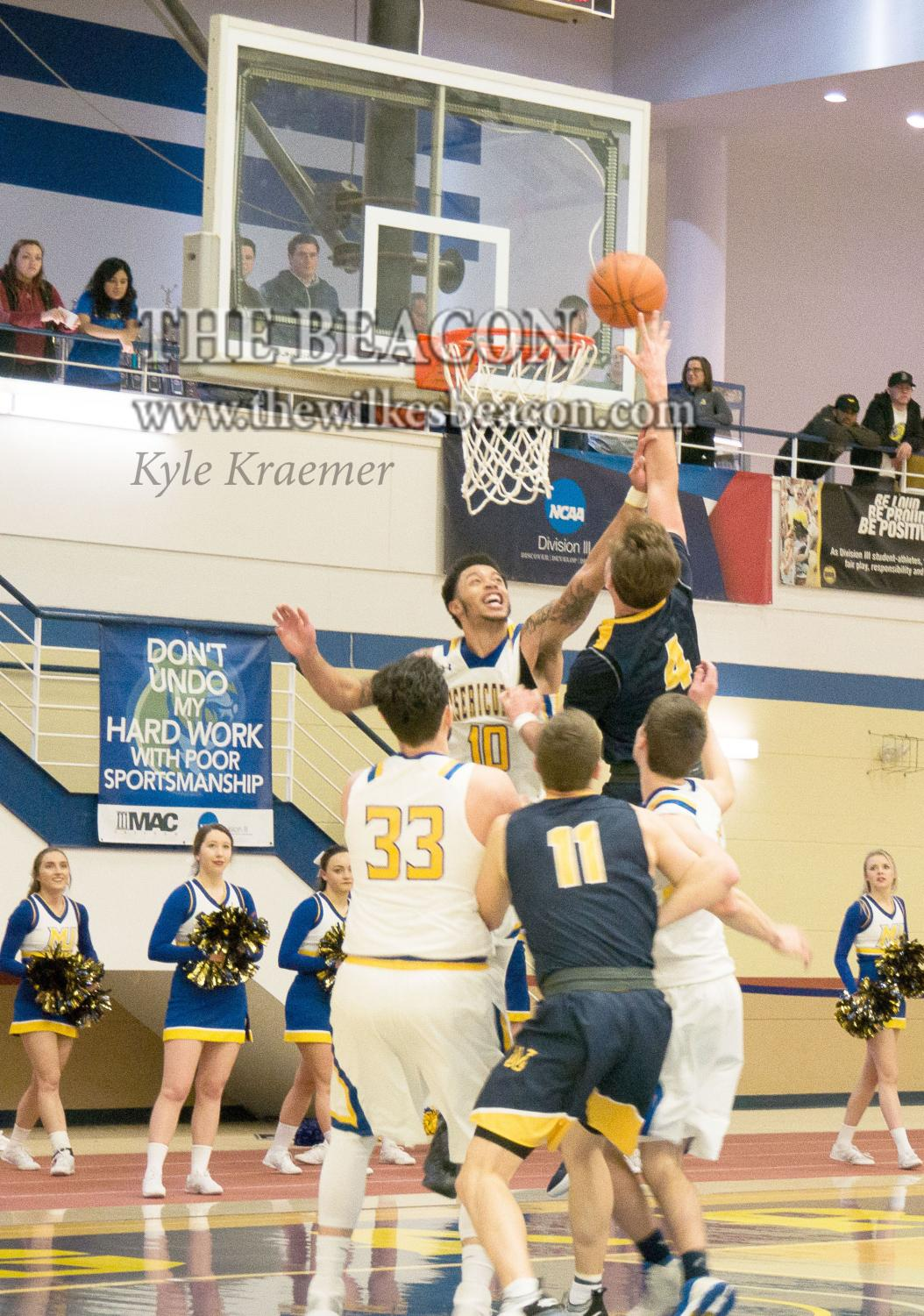 Senior Tommy Bowen secures the basket under the net for Wilkes.