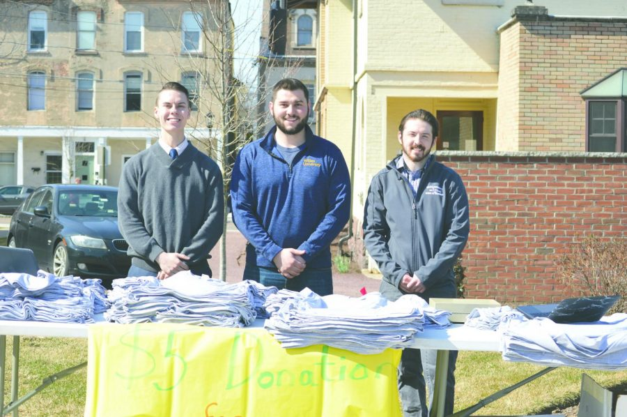 Student coordinators Cody Morcom, Dylan Fox, and Harrison Ferro stand with the table of t-shirts for participants. The walk accepted $5 donations for naloxone for the Wilkes-Barre Fire Department.