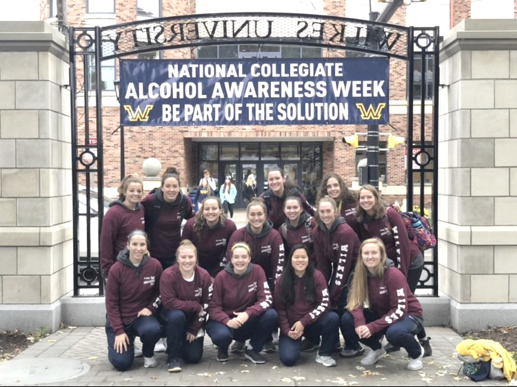 The women's basketball team poses for a photo together before participating in the awareness walk.