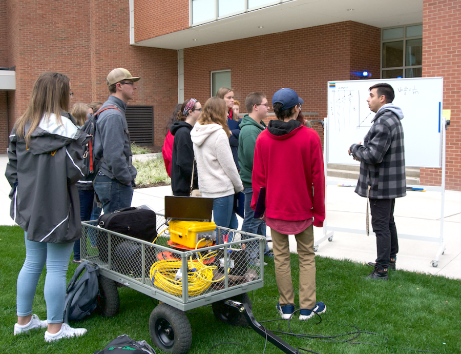 Dr. Bobby Karimi, assistant professor of environmental engineering and Earth sciences, explains to visiting students his station on gravity anomalies.