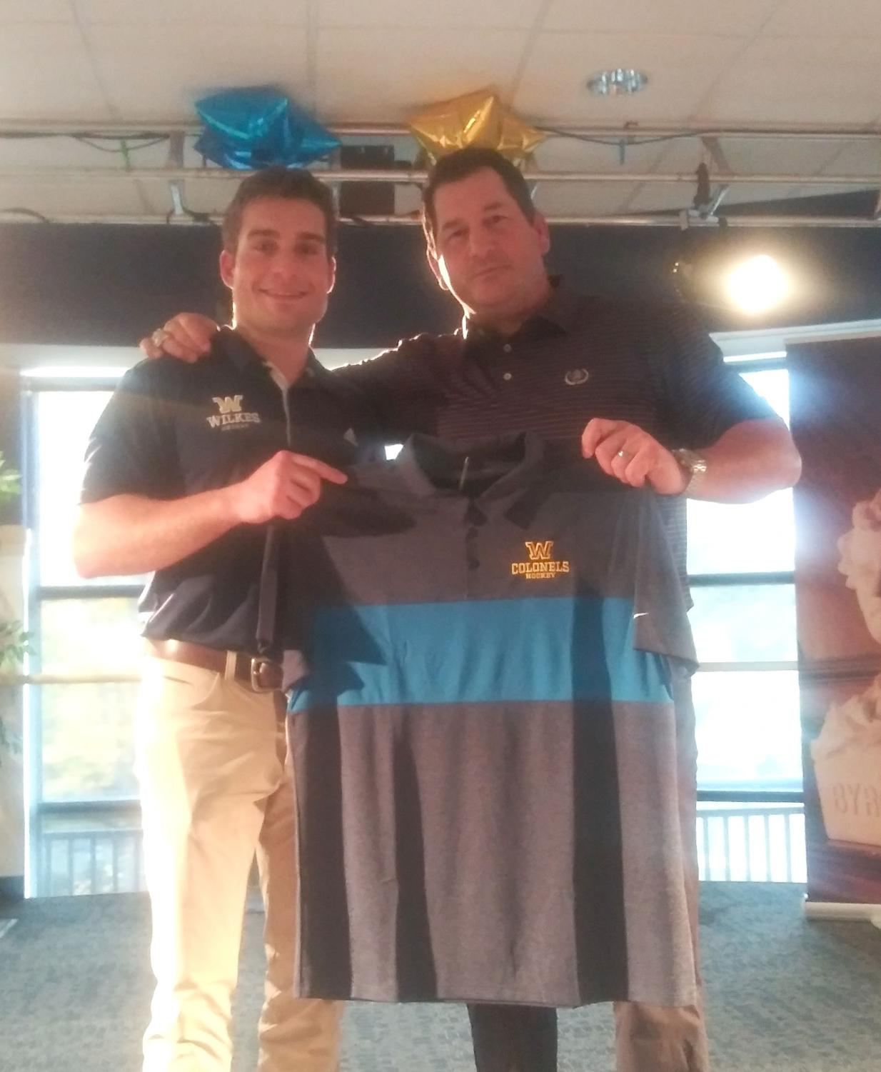 Tyler Hynes, Men's Ice Hockey Head Coach, presents Bonvie with a Wilkes hockey shirt.