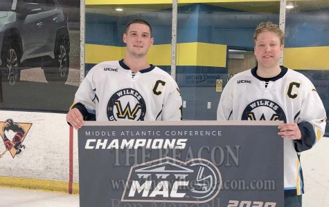 Captains Michael Gurska and Tyson Araujo pose with the MAC banner.