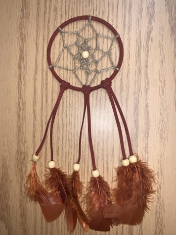 Step 6: Add feathers and beads to complete the dreamcatcher.