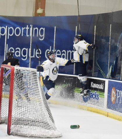 Tyler Barrow (right) jumps into the air in celebration following his overtime goal, as Devon Schell (left) is the first player to greet him.